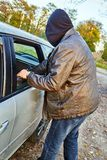Hooligan breaking into car Royalty Free Stock Photography