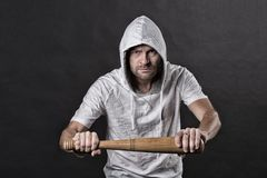 Hooligan hold baseball bat. Bearded man wear hood in hoodie tshirt. Gangster guy threaten with bat weapon. Aggression or. Anger and violence concept, vintage royalty free stock image