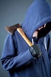 Hooligan - person with an axe. A mean woman holding an axe and wearing a hooded top Stock Photos