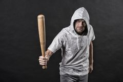 Hooligan wear hood in hoody, fashion. Man hold baseball bat, aggression. Gangster guy threaten with bat weapon. Aggression, anger. And violence concept, vintage royalty free stock photography