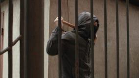 Hooligan in zich masker het uitrekken met knuppel terwijl het wachten van iemand achter de omheining op straat stock footage