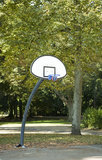 Through the hoop. Basketball swishing through a hoop on an outdoor basketball court in urban park stock photo