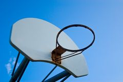 The hoop. Old basketball hoop, no net, against a bright blue sky royalty free stock photography