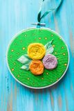 Hoop modern embroidery with botanical motifs on a wooden background Stock Photos