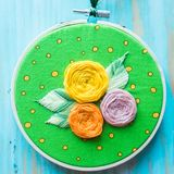 Hoop modern embroidery with botanical motifs on a wooden background Stock Image