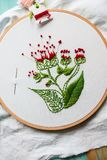 Hoop modern embroidery with botanical motifs on a wooden background Stock Photo