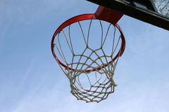 Hoop on a sunny day. Basketball hoop and net against a blue sky royalty free stock photo