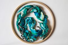 Hoop with threads of green tones for embroidery. Top view. Beige Royalty Free Stock Photo