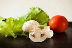 Hoop van Champignonspaddestoel op zwarte pan met tomaat en salade Stock Foto