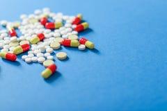 Hoop van diverse die pillen op blauwe achtergrond met exemplaarruimte worden geïsoleerd voor uw tekst stock afbeeldingen