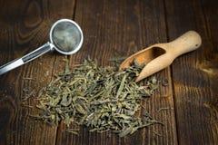 Hoop van droge thee met zeef op natuurlijke houten achtergrond stock afbeeldingen