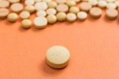 Hoop van geassorteerde beige capsules op oranje lijst Één pil is apa royalty-vrije stock afbeelding