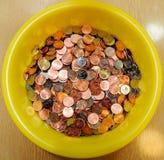 Hoop van muntstukken in gele kom Stock Foto's
