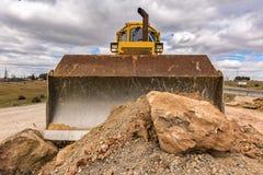 Hoop van steen en aarde die door een geel graafwerktuig wordt bewogen royalty-vrije stock afbeeldingen