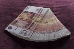 Hoop van vijf duizend Russische roebelsbankbiljetten, stapel op rood fluweel stock afbeelding
