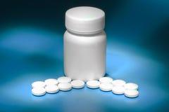 Hoop van witte pillen en een witte pillenfles op blauwe achtergrond Royalty-vrije Stock Afbeeldingen