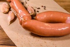 Hoop van worsten, knoflook en kruiden op een bruin verpakkend document stock afbeelding