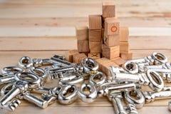 Hoop van zilveren sleutels en houten kubusblok op houten vloer stock afbeelding