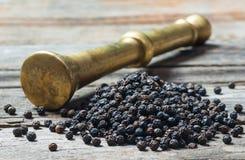 Hoop van zwarte peper en metaalmortier, gemalen peperbollen op houten achtergrond, droog het graanconcept van de kruidpeper stock afbeelding