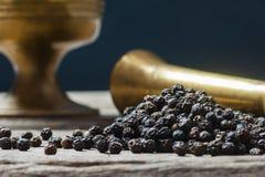 Hoop van zwarte peper en metaalmortier, gemalen peperbollen op houten achtergrond, droog het graanconcept van de kruidpeper stock foto