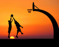 HOOPS. Two young men playing basketball, silhouetted against a majestic sunset Stock Image