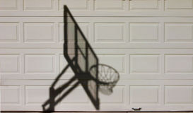 Hoops. Shadow of basketball hoop against garage door Royalty Free Stock Photo