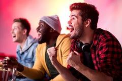 Joyful trendy guys are enjoying football stock images