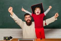 hooray Ojczulka i syna dźwiganie zaciskać pięści w gescie hooray Ojcuje uczyć jej syna w sali lekcyjnej przy szkołą _ fotografia royalty free