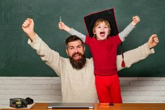 hooray Pappa och son som lyfter grep hårt om nävar i hooray gest Fader som undervisar hennes son i klassrum på skola yeah royaltyfri fotografi