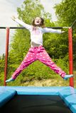 Hooray Trampoline Girl Jump. Happy girl jumping high on a trampoline on a sunny day outdoors Stock Images