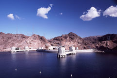 Hoover Dam and Lake Mead. Hoover Dam and intake towers as seen across deep blue waters of Lake Mead with mountains in background and bright sky above Royalty Free Stock Image