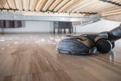 Hoovering il sust sul pavimento di legno Fotografia Stock Libera da Diritti