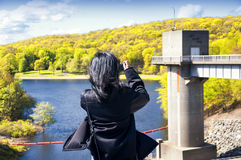 Hop brook dam state park in Naugatuck. A woman taking pictures of  lake side of Hop Brook Dam in Naugatuck connecticut on a sunny blue sky day Stock Photography