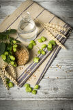Hop flowers, wheat ears and seeds, water. ingredients for brewing beer on wooden table Stock Photo