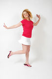Hop and Skip. Woman hops an one foot and lifts the other. On white background full body shot Royalty Free Stock Photos