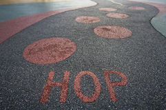Hop written into rubber floor of playground Stock Photography