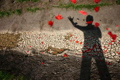 Hope. Dry, cracked earth with pestal of poppies that are thown by a man stock photography