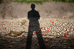 Hope. Dry, cracked earth with pestal of poppies that are thown by a man royalty free stock images