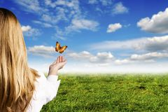 Hope. Girl with open hand and butterflies flying away like a concept for optimistic mood, hope and ecology Stock Photo