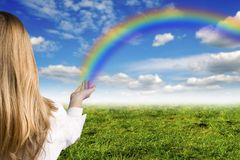 Hope. Girl with a rainbow raising from her hand like a koncept for hope and for ecology Stock Photography