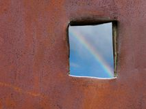 Hope. View on rainbow through hole in a rusty fence Stock Image
