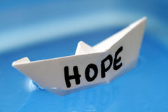 Hope. Paper boat on cyan background Stock Image