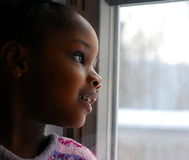 Hope. A young african american girl looks out the window with an expression of hope and happiness