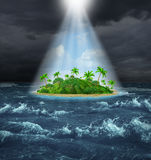 Hope And Aspirations. Success concept with a dark storm ocean background contrasted with a glowing light from above shinning down on a beautiful tropical island Stock Images