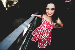 Hope for a bright future. Beautiful bright young girl in a red dress with polka dots against a dark underground passage Royalty Free Stock Photo