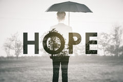 Hope concept. Dull image of young man with umbrella standing outside. Hope concept stock photo