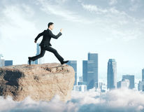 Hope concept. Side view of young businessman jumping off cliff on city background. Hope concept royalty free stock photos
