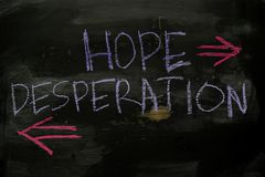 Hope or Desperation written with color chalk concept on the blackboard royalty free stock images