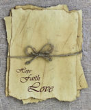 HOPE, FAITH, LOVE on antique worn parchment paper tied in rope on rustic background Stock Photography