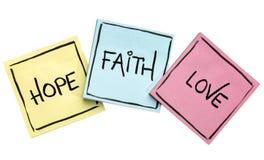 Hope, faith and love on sticky notes stock photos